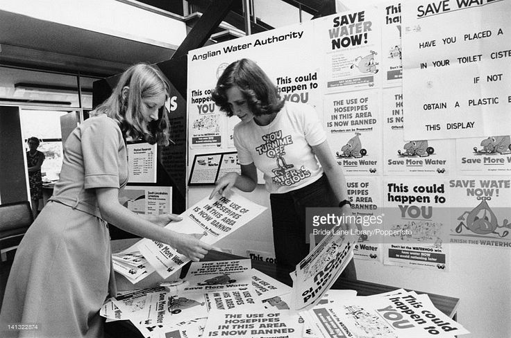 Debbie Tuft (right), of the Anglian Water Authority, and a colleague sort through posters for a campaign to conserve water during Britain's worst drought for 250 years, Pitsford, Northamptonshire, 1st August 1976. Tuft is wearing a t-shirt with a picture of a tap and the slogan 'You turn me off. Water is precious'.
