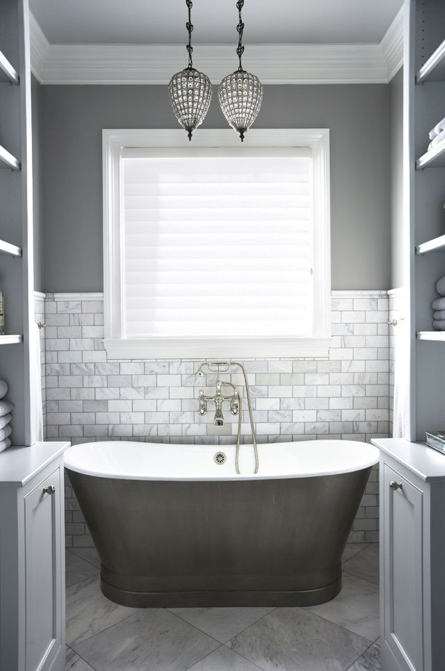 Master Bath | Milestone Custom Homes | Greenville SC | Two built-ins frame the gorgeous free-standing nickel slipper tub, complete with Rohl fixtures. A white Carerra marble backsplash draws the eye down to the same material repeated on the floor.