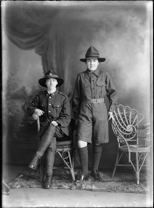 Studio portrait of two unidentified young women in World War I soldier's uniforms, one woman sitting with collar, shoulder and hat badges holding a swagger stick, Christchurch