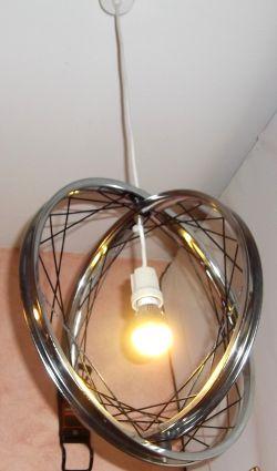 Geflochtene Lampe klein - das Trägerelement besteht aus einer 16 Zoll und 18 Zoll verchromten Stahlfelge (20 Loch), die miteinander verbunden sind. Eine etwa 10 Meter lange Perlonschnur wurde zu einem kunstvollen Netz in beiden Felgen eingesetzt und gespannt. Eine wunderschöne Dekoration und Objekt zur Raumausleuchtung. Seltenes Einzelstück, welches in unserer Kreativwerkstatt gefertigt wurde.