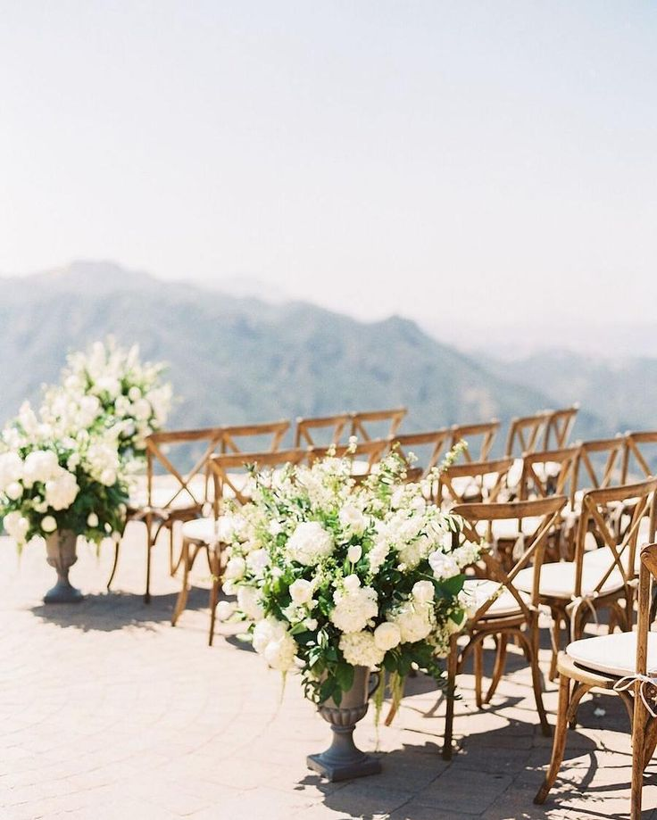 Elegant florals by @heavenly_blooms lined the aisle with @premiere_rents  Vineyard Chairs at @maliburockyoaks.    Venue: @maliburockyoaks   Planner: @sohappitogether   Photography: @sallypineraphoto   Rentals: @premiere_rents   Florals: @heavenly_blooms   Rentals: @foundrentals @casadeperrin   Catering: @wpcatering   Linen: @latavolalinen   Cake: @thebutterend