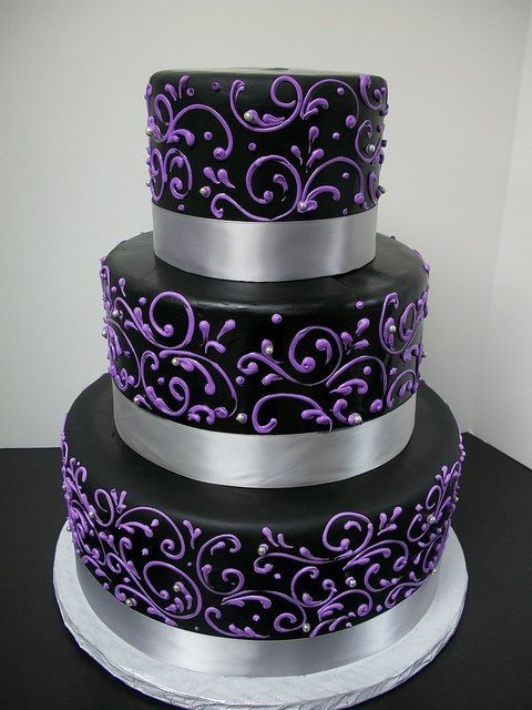 Three-tiered cake with silver bands, black frosting, and bright purple decorative accents