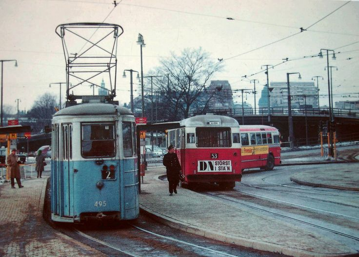 A line 2 tram next to some busses in Stockholm.
