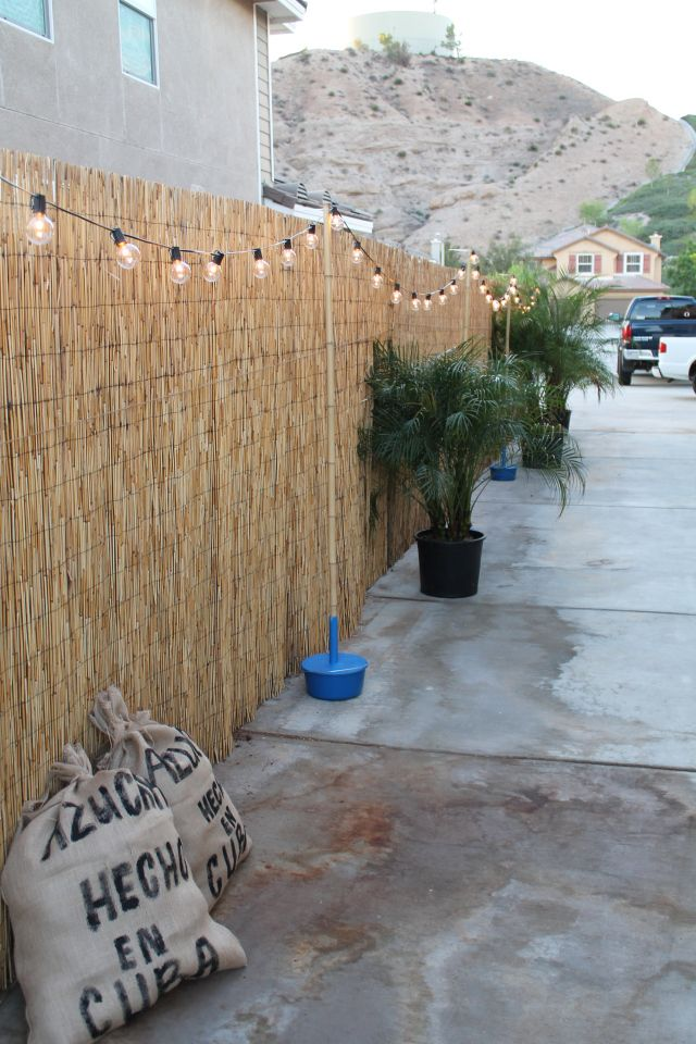 Hemp fencing along the side wall with market lights strung on bamboo in a custom-made bucket.