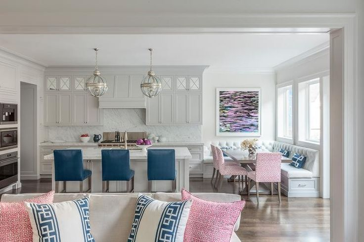 Light gray cabinets and center kitchen island boast a family friendly vibe transitioning into a red, blue and white L- shape banquette.