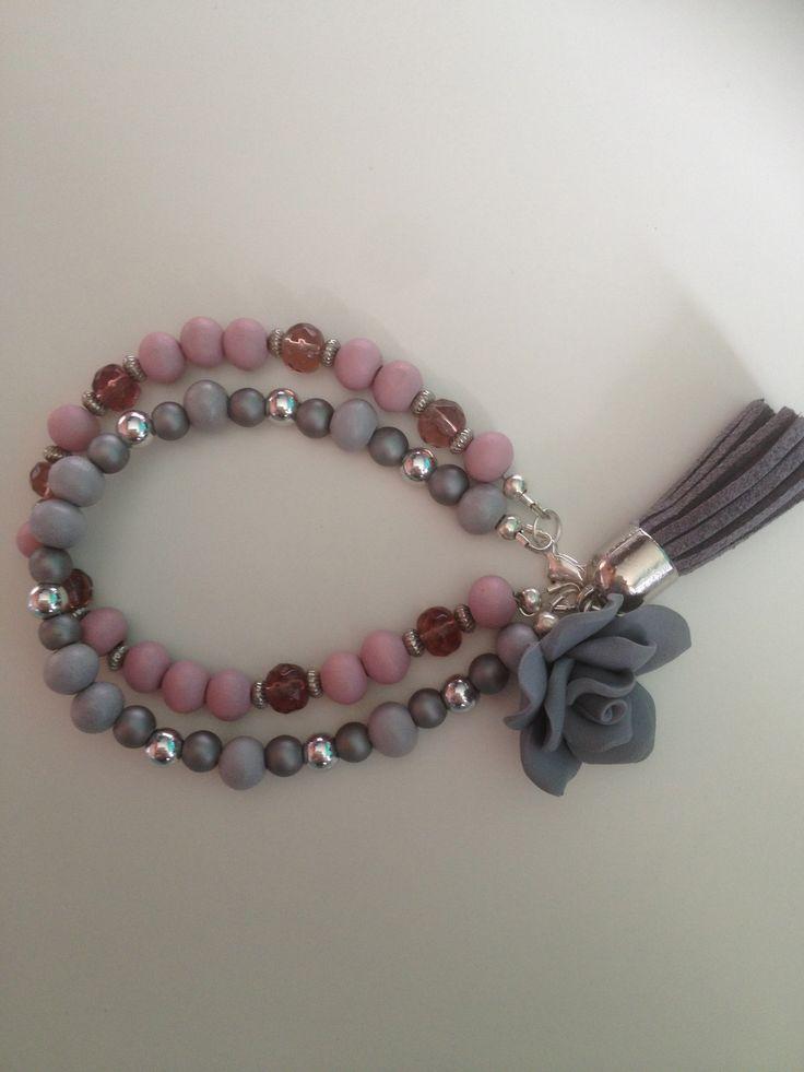 Armband met twee strengen in het grijs en lila met een roos van fimoklei, een kwastje van suede en een slotje.  www.curiousbeads.nl