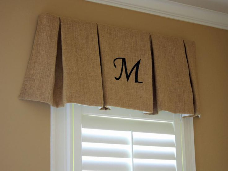 Cheryl from New House to Home elevates inexpensive burlap fabric by folding it into deep box pleats and stapling it to a board to make an easy valance. A stenciled monogram adds even more detail.
