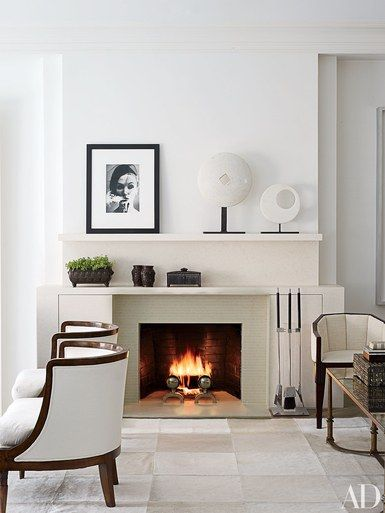 The living room of this New York City apartment, decorated by Penny Drue Baird of Dessins, is just one example how to add Art Deco style to a space. It serves as a gallery for works by, from left, Damien Hirst, William Klein, and Hiroshi Sugimoto. The angular armchairs are 1930s French, the barrel-back | archdigest.com