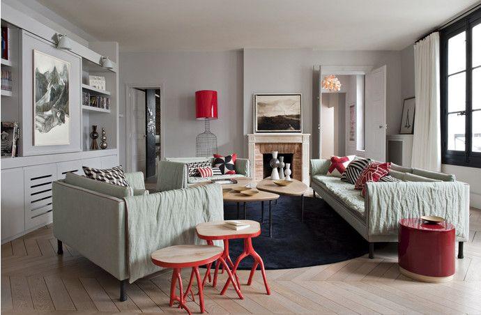 Стены гостиной окрашены в светло-серый цвет и эффект-но контрастируют с черными оконными рамами. Диван и кресла Popi, Caravane, в обивке из светлого льна. На переднем плане — круглые столики из дерева, Tinja, и табуреты из бамбука с покрытыми красным лаком ножками, Ekobo. Черный ковер, Jab. Рядом с камином — торшер, дизайн Марии Кристоф.