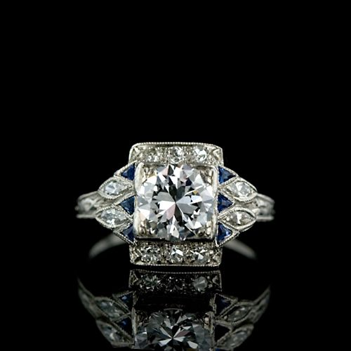 Platinum ladies original Deco ring featuring a high-quality 1.10 carat European cut diamond (E-F color, VS2 clarity, EGL Certified) set in a square box head setting further set with trillion cut sapphires (6 total, .10 carat total weight) and marquise and round cut diamonds (14 total, .27 carat total weight, G-H color, VS2-SI1 clarity). Circa 1925.