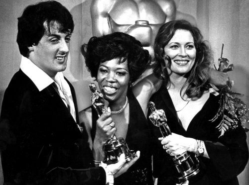 """Writer-actor Sylvester Stallone, star of the Oscar-winning film """"Rocky,"""" congratulates Peter Finch's widow, Eletha, center, after Finch was posthumously awarded the lead actor award at the 1977 Academy Awards. Faye Dunaway, right, won for lead actress."""
