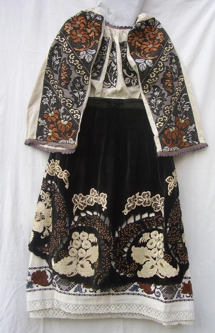 Costum femeiesc din zona de munte a Banatului, ia şi poalele din pînză de in cu motive florale, cusute cu mătase, şorţul din catifea cu motive florale, cusute cu mătase şi paiete.