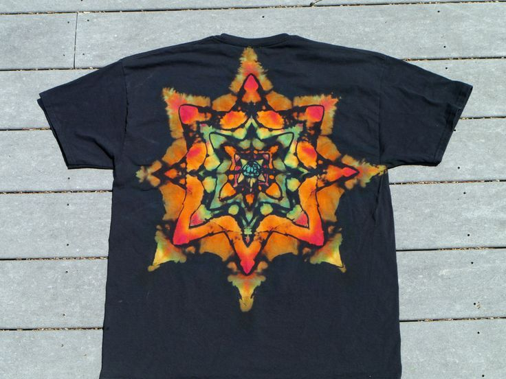 Stained Glass in the Hippy Cathedral: Reverse Tie Dyed Star on Black; Men's XL. This is an example of reverse tie dye with a multi-colored star. Each point is blended with several dyes to create the effect. Dark black lines from the folding pattern accent the design. This design is on the back of the shirt only, making a dramatic yet cool presentation. Men's XL ($22) on The CraftStar @TheCraftStar  #uniquegifts #tiedyedshirts #thecraftstar #wideeyedyes