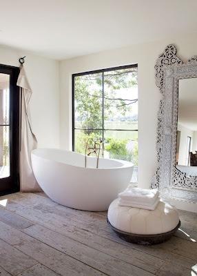 Contraste gagnant entre les courbes simples de la baignoire et du pouf et les motifs entrelacés compliqués du miroir imposant. J'adore !