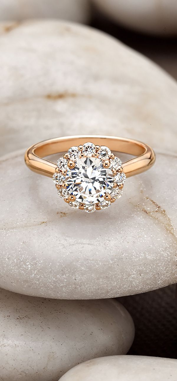 The subtle floral diamond halo blooms around the center diamond in this exquisite ring