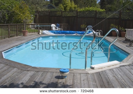 An above ground doughboy swimming pool surrounded by for Above ground pool decks with lattice