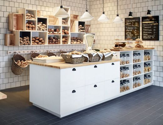 kitchen inspiration - A bakery with open wall shelves filled with newly baked bread and a bench with drawers and open shelves.