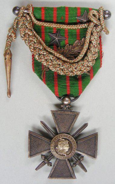 Croix de guerre 1914-1918 en argent, centres en vermeil, en deux parties à l'avers, ruban avec barrette à coulisse chargé d'une palme de bronze, de deux étoiles d'argent et d'une étoile de bronze, et d'une fourragère miniature aux couleurs de la Croix de guerre (décolorée)