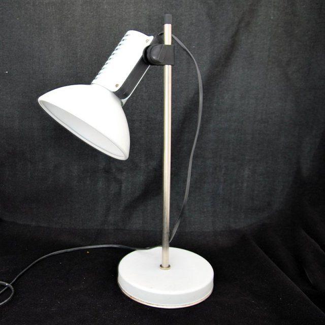 """Klasyk! Biała lampka na biurko """"Art"""" pochodząca z całego systemu (System lamp Art) które zaprojektowali w 1981 roku Bartłomiej Pniewski, Andrzej Tomasz Rudkiewicz dla """"Polam – Wilkasy"""". Uchwyt zaciskowy umożliwia ustawienie dowolnej wysokości oraz kąta pochylenia klosza. Zalecana moc żarówki max 60W. Lampkę można było podziwiać na wystawie """"Rzeczy pospolite"""" w Muzeum Narodowym w Warszawie na przełomie 2000 -2001 roku.  Lampa Wymiary: wysokość 46 cm średnica klosza 17 cm średnica podstawy 16…"""