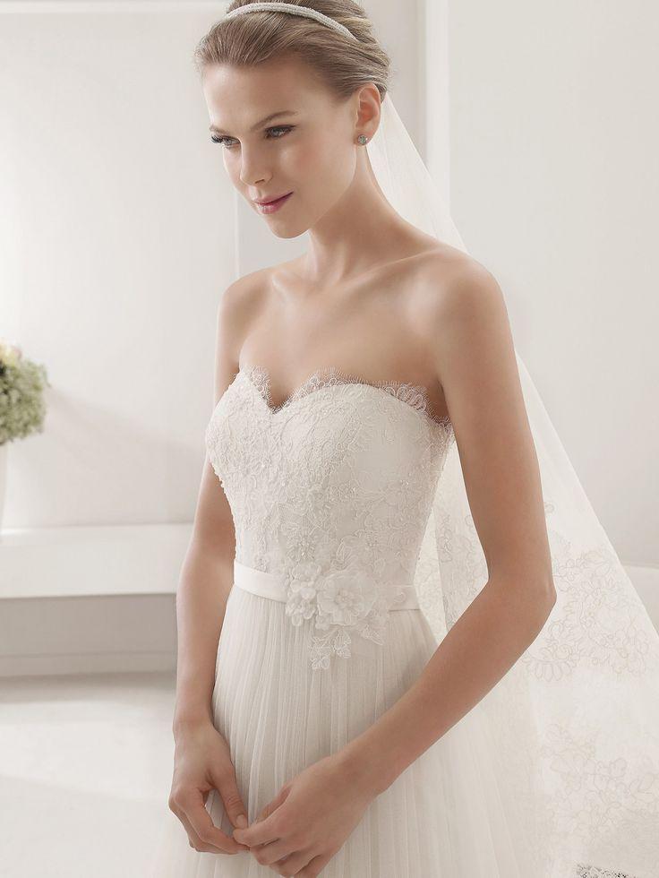 Элегантное свадебное платье с кружевным болеро, дополняющим открытое декольте в форме сердца. Ажурная ткань романтично скрывает плечи и подчеркивает форму шеи.  На талии, выделенной А-силуэтом свадебного платья, расположен узкий пояс с объемной отделкой в виде нескольких цветков из ткани.  Многослойная объемная юбка из тюльмарина ниспадает до самого пола, сзади переходя в красивый полупрозрачный шлейф средней длины.  Свадебное платье из коллекции 2015 года
