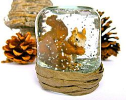 Schneekugel selber machen: Schraubgläschen, Figur aus Plastik, Kunstschnee / Glitter o.ä., destilliertes Wasser und etwas Spülmittel, Heißklebepistole, Geschenkebank.
