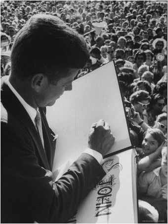 John F Kennedy during Campaign signing his autograph