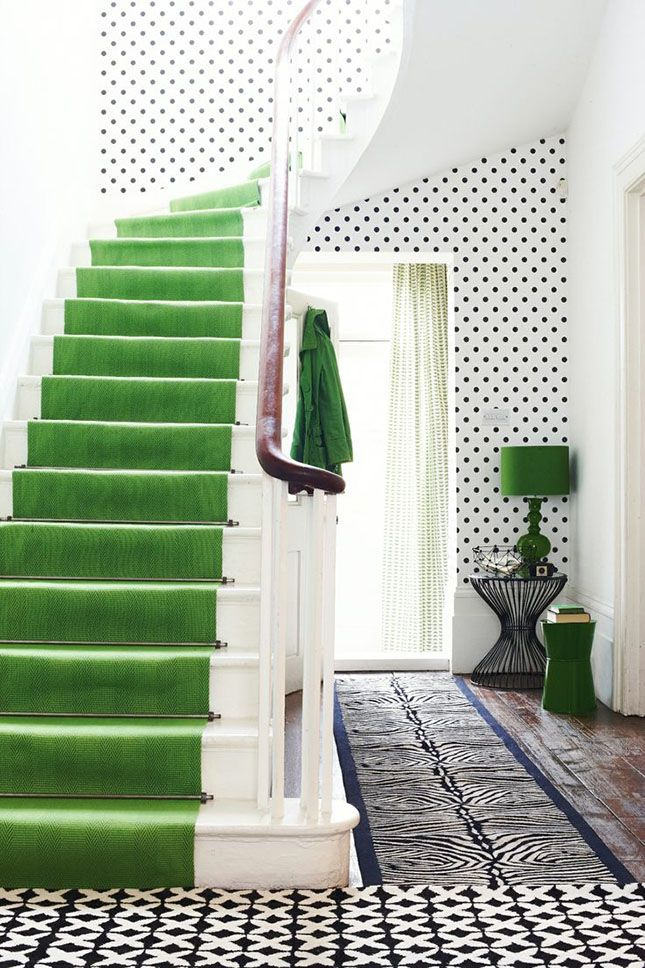 If you're feeling a little bolder and braver, try a much less subtle use of green and make a real style statement with a bright hit of green somewhere in your home. Here, the emerald green velvet staircase contrasts with the fun wallpaper to create a really exciting and engaging space.
