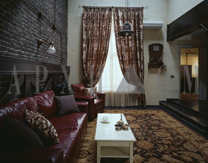 Журнальный столик, выкрашенный в белый цвет, и белые занавески разбавляют вишнево-коричневые оттенки в интерьере гостиной.