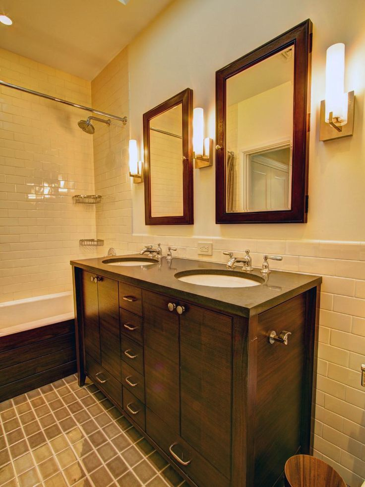 This master bathroom features a walnut double vanity built in the simple, functional lines hailed by the Arts and Crafts Movement, Subway tiled walls in a buttery yellow and floor tiles in a green-beige accentuate the Craftsman look. Period sconces on either side of the vanity mirrors tie the bathoom to the past.