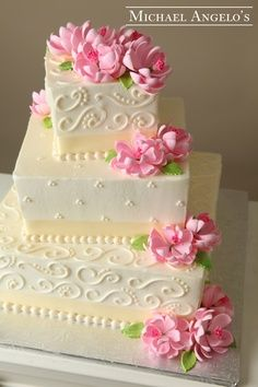 Lotus cake with pastel pink lotus flowers descending down the tiers with curls and swirls accenting, and pearl beads lining them.