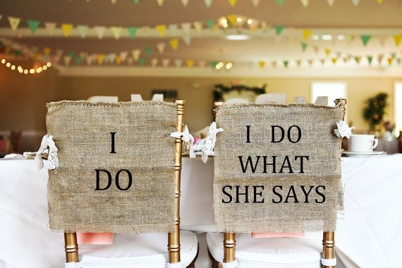 Give your guests a laugh with a pair of handcrafted burlap chair covers that read I DO & I DO WHAT SHE SAYS. Each sign is left open on the sides