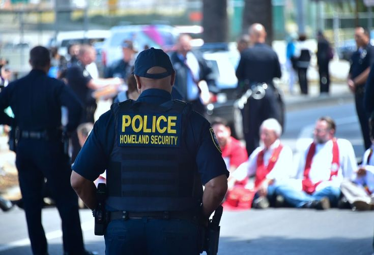 A Department of Homeland Security officer watches as police arrest demonstrators protesting recent enforcement actions by federal Immigration and Customs Enforcement (ICE) outside the ICE headquarters on downtown Los Angeles, California.