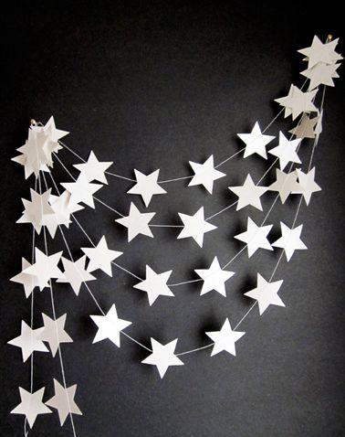 Une guirlande de Noël à réaliser soi-même avec des étoiles découpées dans du carton blanc et collées sur du fil de nylon ou de la laine blan...