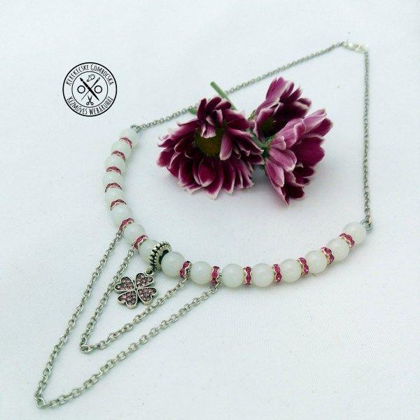 Gyöngyös, strasszos nyaklánc szerencsehozó medállal - 2990 Ft  Opálos gyöngyökkel, strasszos pink elemekkel, szerencsehozó négylevelű lóhere medállal és láncokkal díszített, ívelt, antikolt ezüstszínű nyaklánc. A nyaklánc hossza: 43 cm
