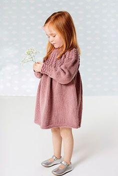 Den søde pigekjole i blød bomuld/uld-blanding får facon af partierne med snoninger på bærestykke og ved håndled.
