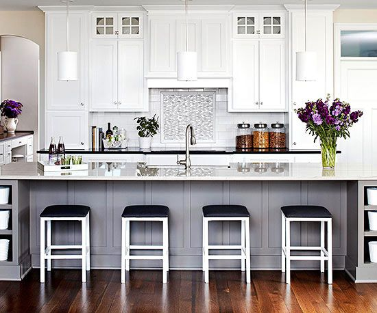The crisp white cabinets go to the ceiling and create a spacious feel, while the large gray island adds weight, plus plenty of seating and prep space. Touches of black add to the room's glamour.