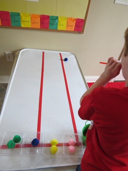 Five fun ways to teach with tape | Teach Preschool - using a board and tape for a game with pom poms and straws.