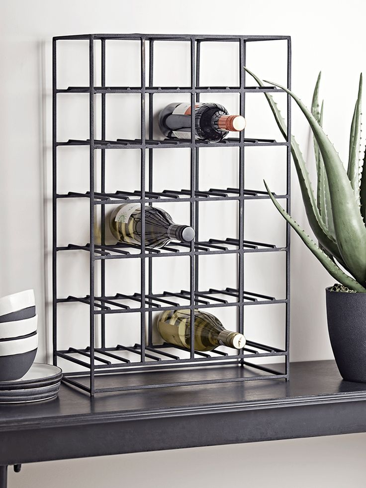 Crafted from black iron in a simplistic rectangular shape, our industrial-inspired wine rack can fit up to 24 standard sized wine bottles.  Free standing, with a sturdy frame, this elegant piece will look wonderful on your kitchen surface or tucked away under the counter.