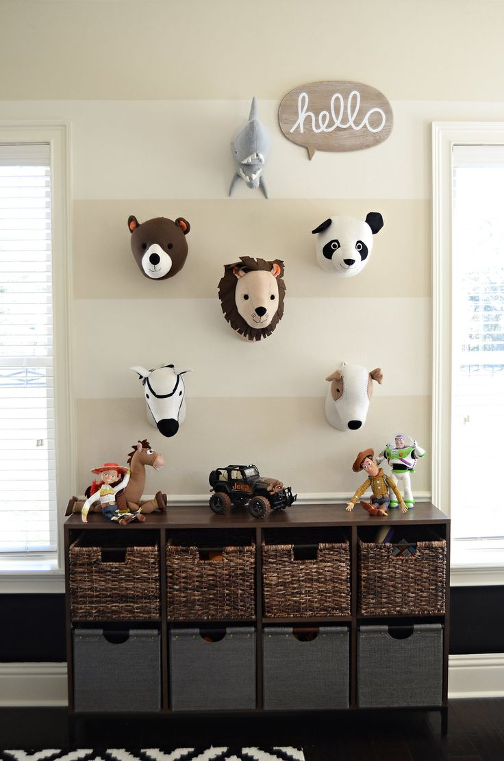 Toddler + Teen Playroom on the blog! Target animal heads, chalkboard walls, tone on tone stripes, threshold bookcase from Target, milk crate wicker baskets and Wayfair black and white rug. Design by Evans Construction & Design in Gainesville, FL