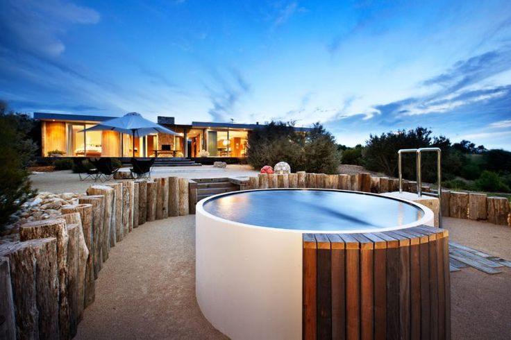 small contemporary round backyard hot tub design that look great surrounded by weathered tree trunks