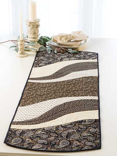 """An easy project to whip up for the holidays! This table runner and place mat pattern is perfect for all those large-scale prints that have been giving you that come-hither look. Quick-to-stitch and super trendy, the finished project makes for a great gift for any special person in your life. You can jazz up the finished look by add some extra stitches here and there, embellishments, and your favorite fabrics. Finished sizes: Table runner: 15"""" x 47"""" Place mats: 14"""" x 18 1/2"""" each"""
