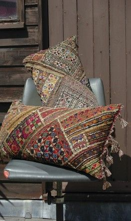 Artfully hand made embroidered cushions made of old tribal fabrics and tasselled at each end.
