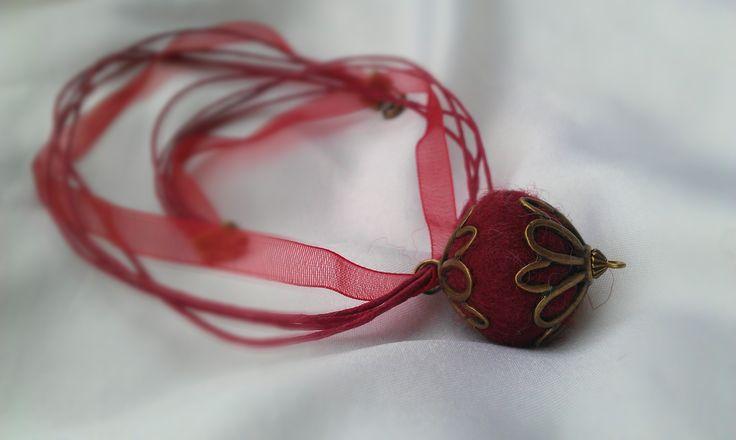 Piros nemezgolyós nyaklánc, szatén szalagon, réz gyöngykupakkal. Más színben is, 1.800,-