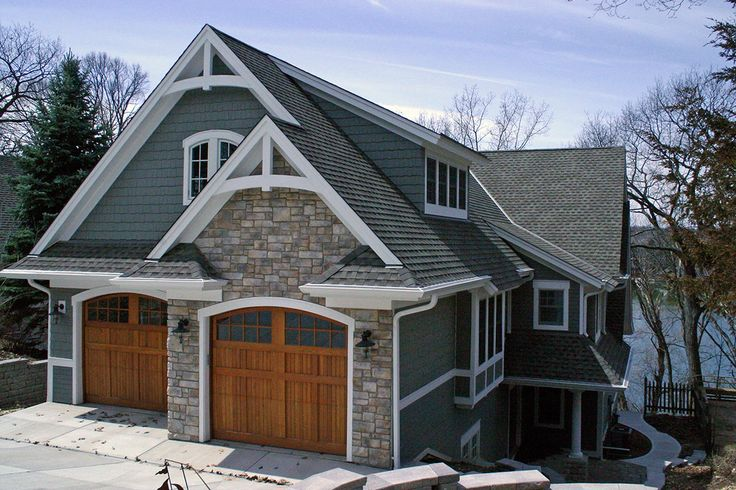 Road side exterior view with arched gable brackets, wood stained custom garage doors, and bonus space above garage