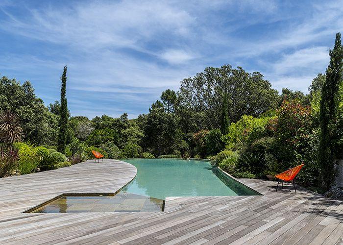 Vert Turquoise est à la fois piscinier et paysagiste, ce qui explique la parfaite intégration de la piscine à son environnement. Le bois fait une jonction naturelle entre l'eau et la végétation omniprésente.