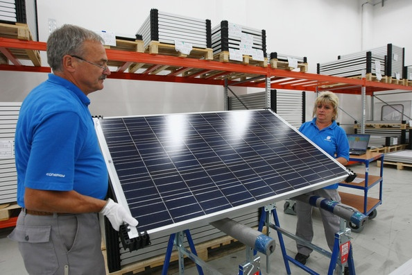 Workers at a production plant of German solar panels maker Conergy do a quality check on finished panels on August 19, 2009 in Frankfurt (Oder), Germany. Conergy is expanding its production capacity in order to meet increasing worldwide demand for solar energy.