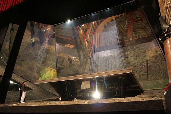 O palco do Teatro Verdi de Padua durante a instalação. No centro da plataforma inclinada, que ocupa todo o palco, há uma escotilha grande que durante a ópera, irá revelar ao público a existência de um ambiente abaixo. O espaço do palco se reflete em duas pernas trapezoidais e um grande cenário ZSM - Espelho Mágico de 11 m altura e 14 m de largura que formam, em relação ao plano inclinado do palco, um ângulo de 90°. Através da ZSM - Espelho Mágico pode ser visto na transparência algo como um…