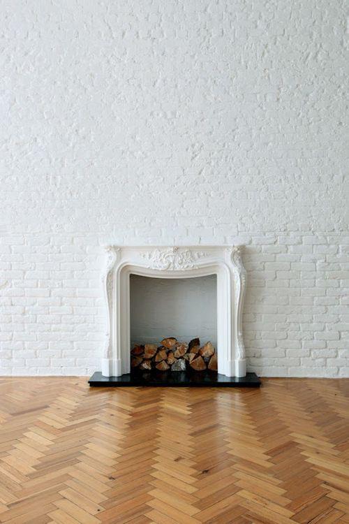 herringbone floor, white brick wall and fireplace
