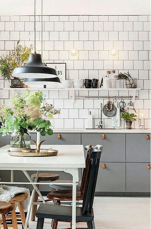 Beautiful Scandinavian style kitchen with grey cabinets industrial lighting and lovely leather pull handles