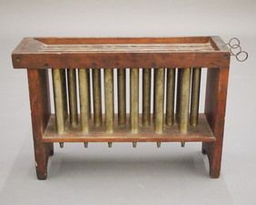 "A 19th century floor model 18-tube candle mold. Mixed wood frame construction with simple cut out feet and iron tubes. Old surface with some wear. 24"" long overall."